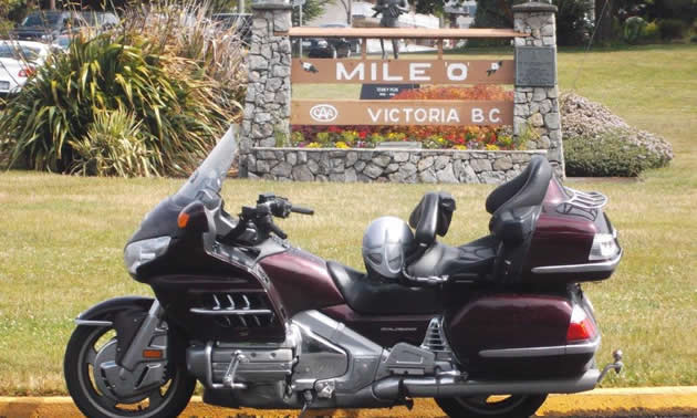 A motorcycle parked in front of Mile 0 sign in Victoria.