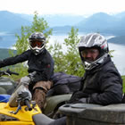 Two guys sitting on ATVs by a lake