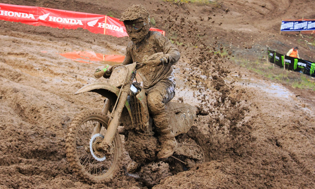 A guy on a dirt bike covered in mud.