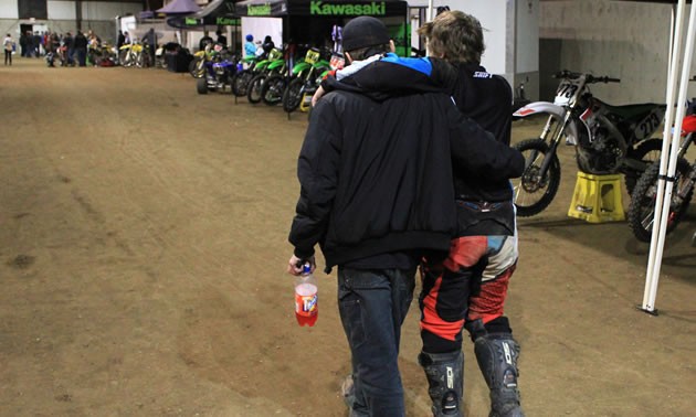 A father helping his son across the dirt track.
