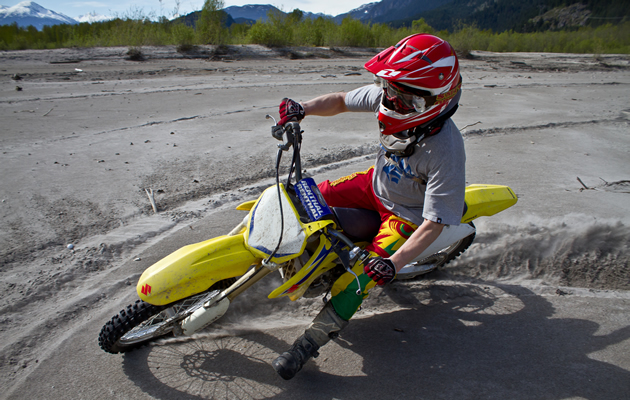 Sean Nicol spins donuts on his dirt bike in the sand.