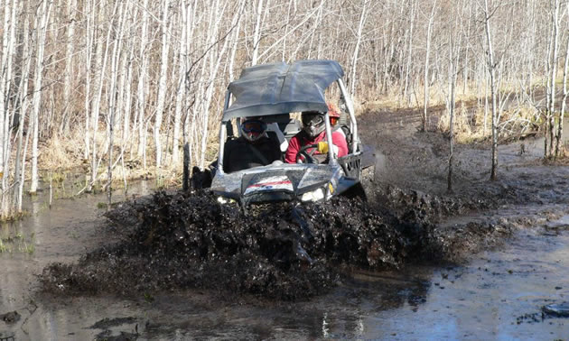A side by side going through deep mud.