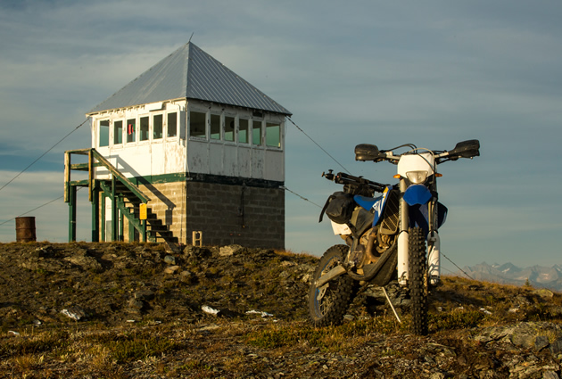 A dirt bike parked by a fire lookout tower.