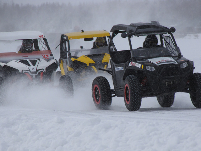 Three side-by-sides ice racing on a cloudy winter day.