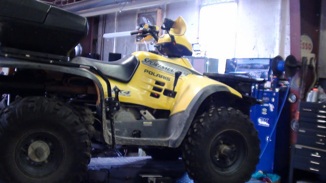 A photo of a yellow ATV in a garage.