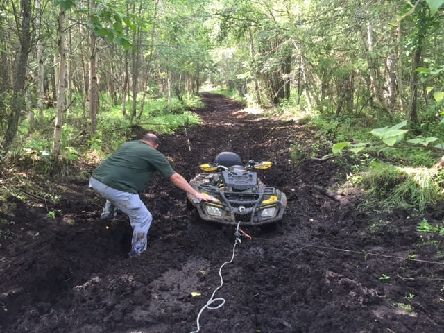 Pulling an ATV by winch out of a mud hole in the centre of a trail.