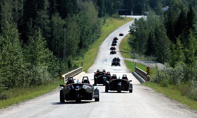A group of Slingshot riders are cruising down a side road single-file.