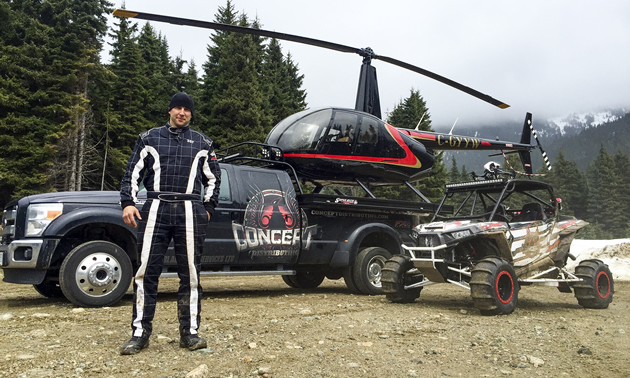 Al McBeth standing beside a truck with a helicopter on it and a custom Polaris RZR side by side.
