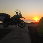 Photo of a bike on a concrete pad beside a yellow tent with the sunset in the background.