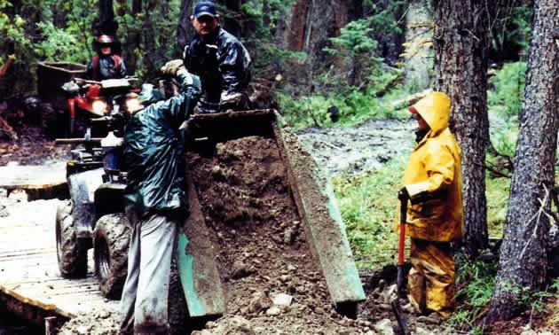 ATVers dumping dirt onto a trail.