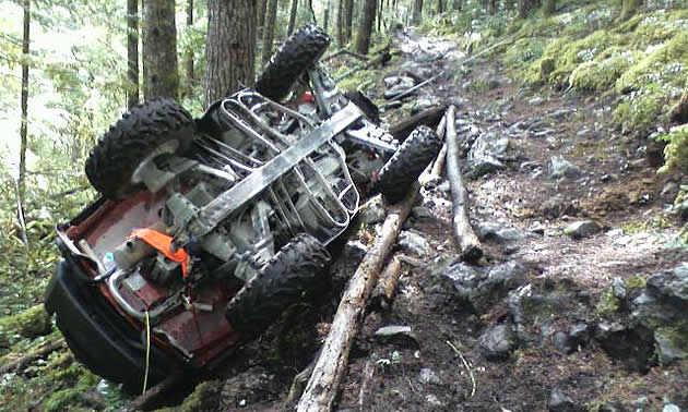 An ATV that's flipped over and hung up on a tree.