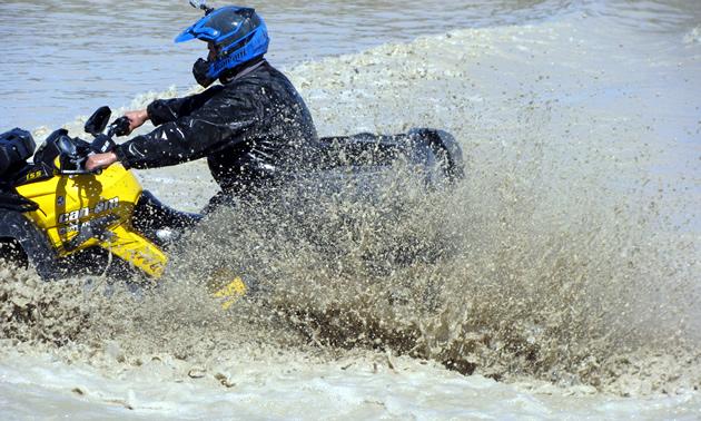 An ATVer riding through a deep mud pit.