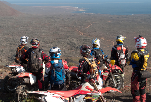 A group of motorcycle riders looking down at the Baja landscape.