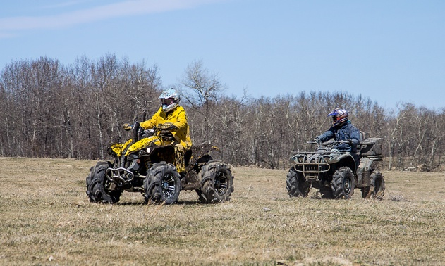 2 Riders on ATV's wearing protective helmets.