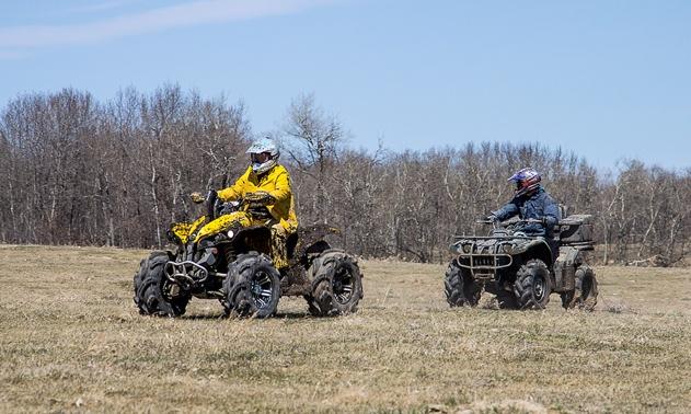 2 Riders on ATV's wearing protective helmets.