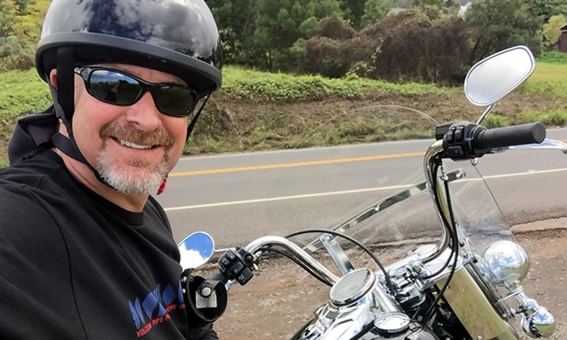 Roger Rhodes taking a selfie on a Harley-Davidson motorcycle.