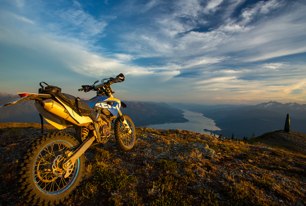 A dirt bike parked on the top of a mountain overlooking a large river.
