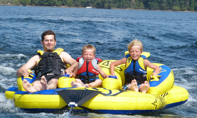 A man with two kids on a three-person inner tube.