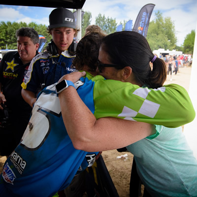 Tyler Medaglia's mom hugging him on the podium after a race.