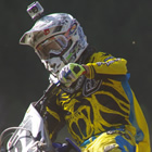 Photo of a young man dressed in yellow riding gear on a blue dirt bike.