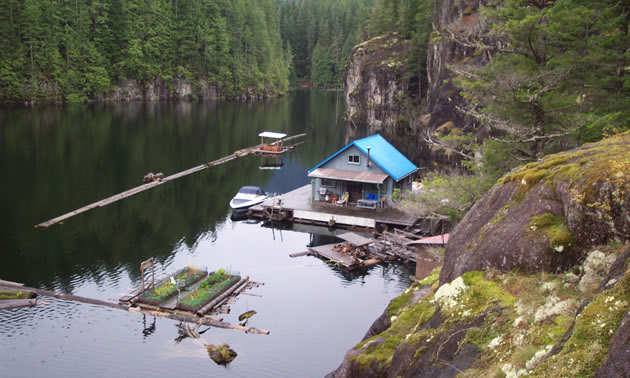 A small floating cabin on the lake with granite cliffs sheltering it.