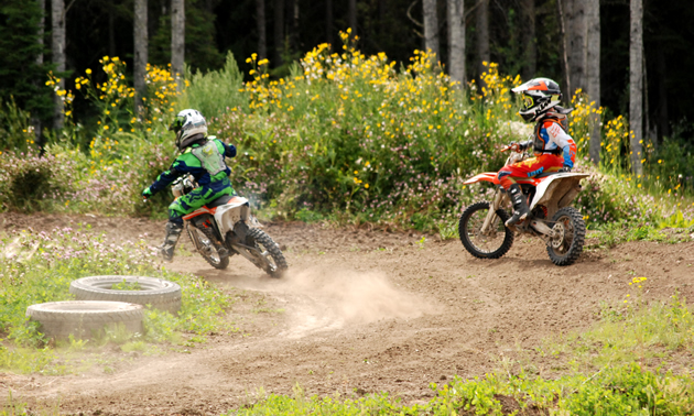 One young rider watches another practice laps on the motocross track.