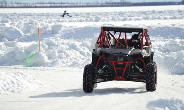Al McBeth rounding a corner in his Polaris RZR during an Alberta ice race.