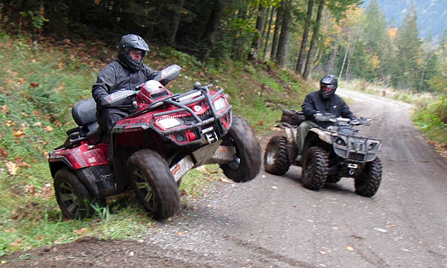 Two ATVers riding on a Forest Service Road.