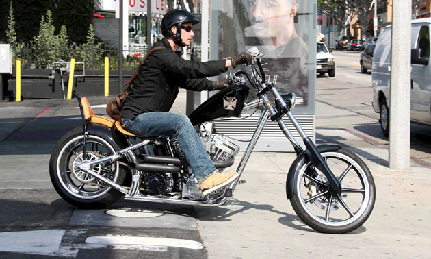 Keanu Reeves riding a chopper motorcycle.