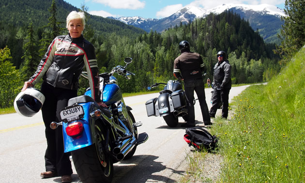 A blonde haired woman standing beside a motorcycle with the Kootenay mountains in the background.