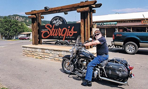 A man sitting on a Harley in front of the Sturgis sign.