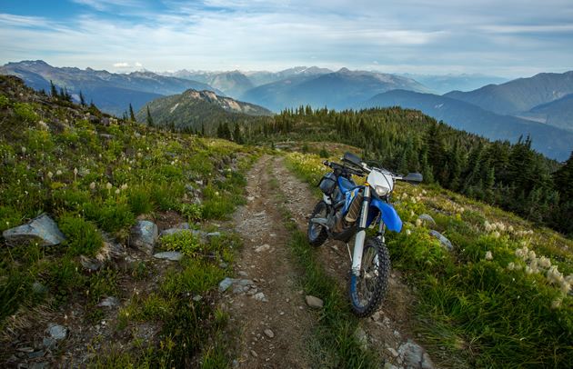 A dirt bike parked alone a mountain trail.