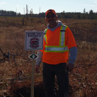 Gary Hora is standing beside signage for one of the trails maintained by the Woodridge Sandhogs.