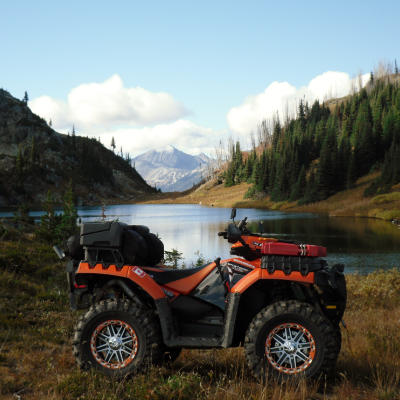 An ATV idles near a lake and mountains.