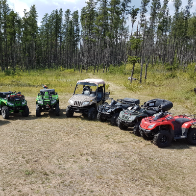 Gary Hora's family owns a collection of quads, which are lined up in front of a forest.