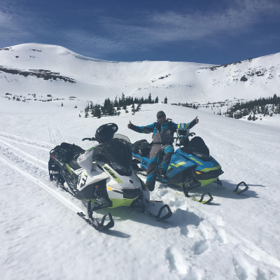 Allan Bouchard smiles on his snowmobile in the backcountry.