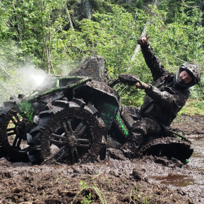 Chris Black gives a thumbs-up as he plows his way out of a large mudpuddle.