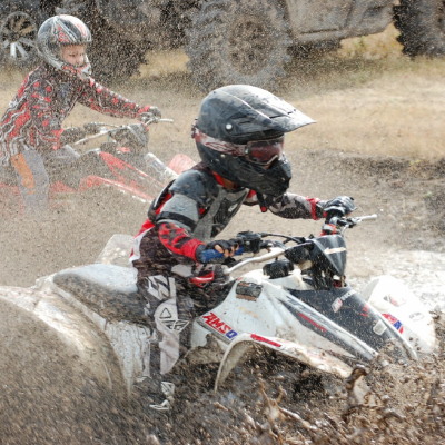 Aiden Lawrence splashes through mud as he powers past a competitor in a race on his ATV