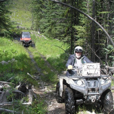 Bob Bogula rides a black ATV on Ridge Trail, followed by an orange UTV in the background.