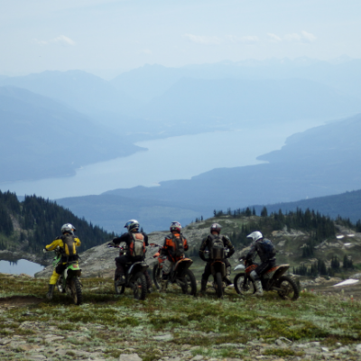 Dirtbikers enjoy the view above Paint Lake with Arrow Lake in the background.