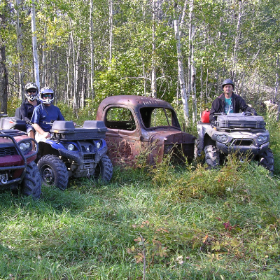 Three quadders line up their vehicles next to a rusted piece of a truck in the woods.