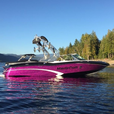 A purple wakeboarding boat idles on a lake.