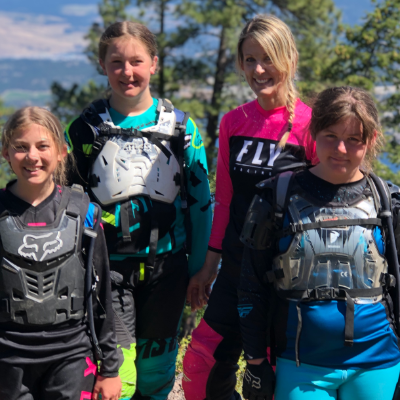 A woman and her three girls wearing motocross gear.