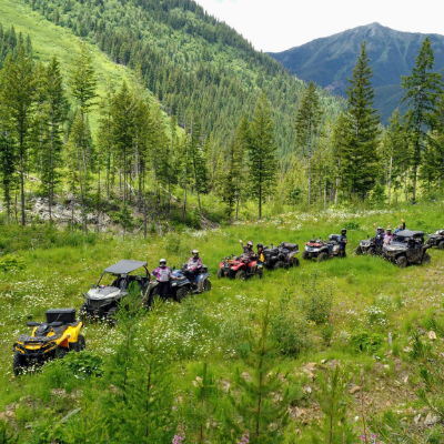 ATVs ride in a row in the foothills of nearby mountains.