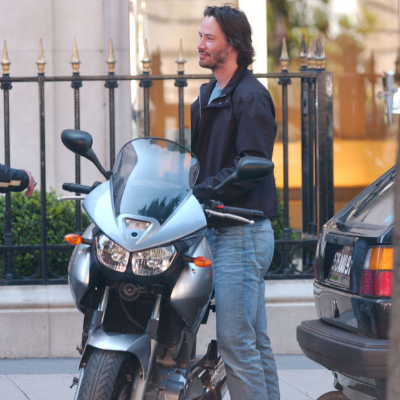 Keanu Reeves smiles as he prepares to ride his motorcycle.
