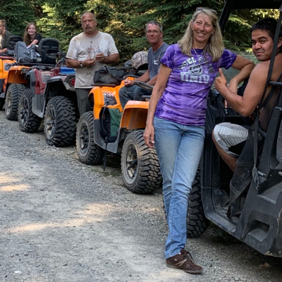 A row of ATVs line up on a trail.