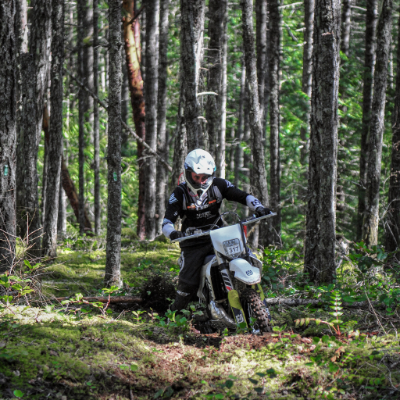 Kitt Stringer riding a dirt bike in a dense forest at the Kirk