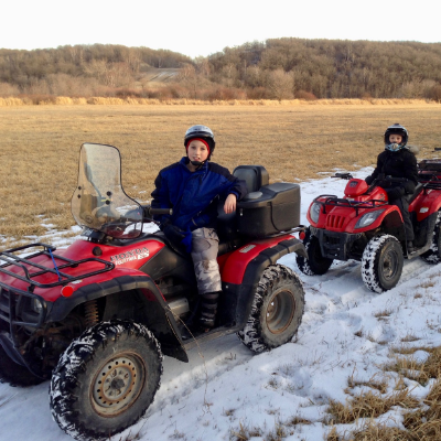 Three ATVs are lined along a snow-covered trail in an open field.