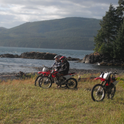Two dirt bikers sit on their bikes and take in the scenery of ocean, mountains and trees.