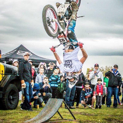 Sam King performs a mini flip on his dirt bike in front of a crowd.